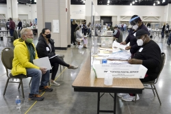 Election workers verify ballots as recount observers watch.