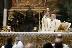 Pope Francis holds up a chalice during mass