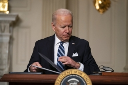 President Biden signs papers behind an official presidential podium.