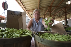 Woman grabs pea pods at farmers market