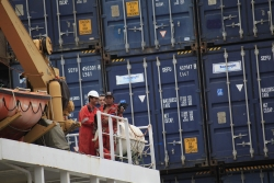 Crew members watching as cargo ship is offloaded