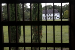 A plantation house seen through bars