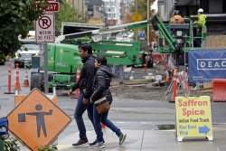 Pedestrians walk past a construction site near Amazon's South Lake Union headquarters in Seattle