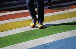 A pedestrian in rainbow shows in a rainbow crosswalk