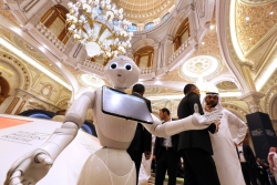 A robot welcomes participants to the Future Investment Initiative forum