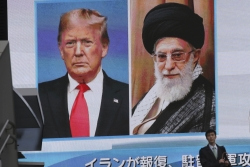 A man walks by a screen showing Donald Trump and Iranian Supreme Leader