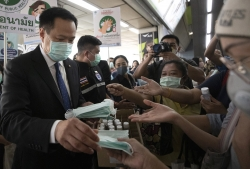 Thai official distributes face masks at skytrain station in Bangkok