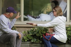Woman with coronavirus waves to family from window of her nursing home.