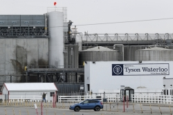 In the distance, a worker leaves a giant Tyson Foods plant as a car drives by in the forefront.