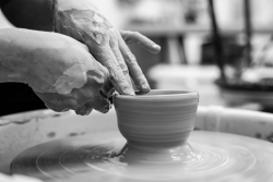 Person shapes pottery on wheel