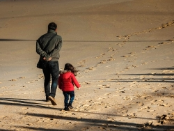 father and daughter walking on a beach