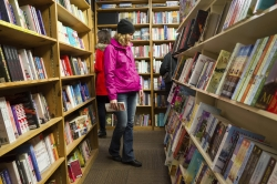 Shoppers browse among narrow rows of books