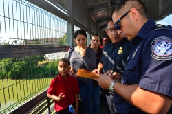 U.S. Customs and Border Patrol agents process a Cuban family, whose turn had been called to cross into the U.S. and apply for asylum.