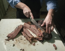 Eddie Deen, owner of Eddie Deen & Company Catering, slices brisket at his company in Terrell, Texas