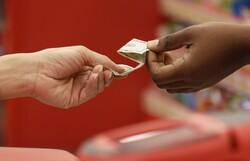A customer hands cash to a Target employee