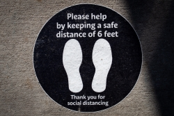A sticker on the ground indicates that people should maintain social distance