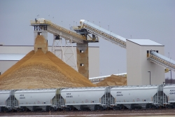 Frac sand piles up at a. processing plant in Chippewa Falls, Wisc.