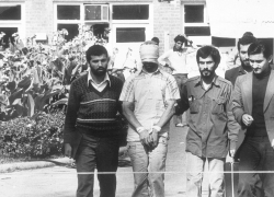 One of the hostages held at the U.S. Embassy in Tehran, Iran is shown to the crowd by Iranian students.