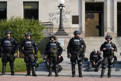 Police in riot gear stand outside the Kenosha County Court House