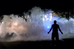 A protester attempts to continue standing through a cloud of tear gas fired by Kenosha police.