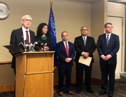 Governor Evers in front of a podium with cabinet officials