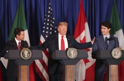 President Donald Trump reaches out to Mexico's President Enrique Pena Nieto, left, and Canada's Prime Minister Justin Trudeau as they prepare to sign a new United States-Mexico-Canada Agreement.