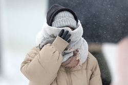 A woman braces in a stiff wind and blowing snow in Chicago.