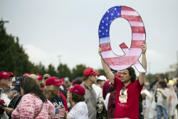A protester holds a Q sign outside a rally for President Donald Trump in Pennsylvania.