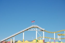 The structure of a roller coaster track with a bright blue, cloudless sky behind.