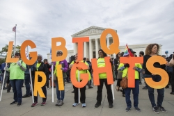 Supporters of LGBTQ rights hold placards in front of the U.S. Supreme Court