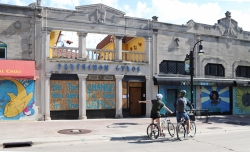 Two bicyclists look at art on boarded-up windows on State Street