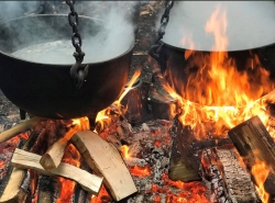 Maple sap boiling in cast iron pots over an open fire