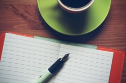 Empty journal with cup of coffee.