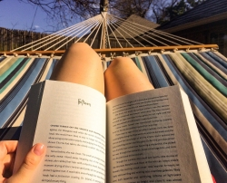 Reading a book in a hammock.
