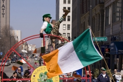 Man dressed as leprechaun on top of giant wheel, Irish flag in foreground
