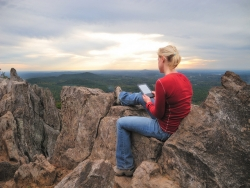 Person reading a Kindle on a mountain