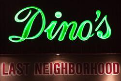 "Bar sign says ""Dino's Last Neighborhood..."""