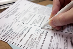 A person fills out a ballot