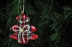 Plaid Christmas tree ornament hanging on tree.