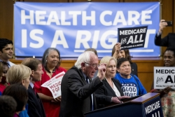 """Bernie Sanders speaking at a podium with a crowd and a banner that says """"Health Care Is A Right"""""""