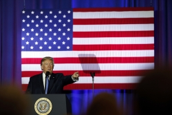 President Trump stands and points at a podium in front of a giant American flag.