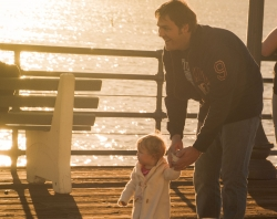 Father and toddler daughter walking on dock near water