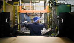A factory worker operating equipment.