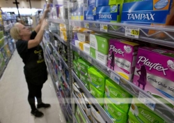 Woman stocks tampons shelf