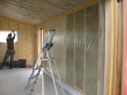 worker putting up insulation