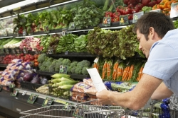 Man looking at list at grocery store