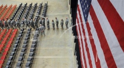 Wisconsin military members file into room with flag