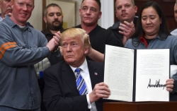 President Donald Trump holds up a proclamation on steel imports