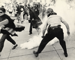 Students flee from police officers spreading tear gas outside the Commerce Building (now Ingraham Hall) at a protest against Dow Chemical, October 18, 1967.