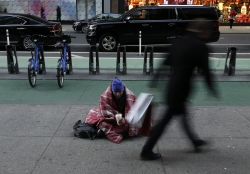 homeless person sitting on the sidewalk